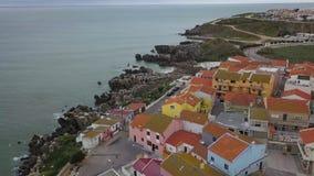 Metragem aérea de uma vista bonita que negligencia a costa rochosa, casas e as casas da cidade Peniche, Portugal Oceano Atlântico video estoque