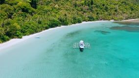 Metragem aérea do barco de turista da lupulagem de ilha perto do Sandy Beach tropical na lagoa rasa de Cadlao do azul de turquesa filme