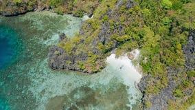 Metragem aérea do círculo da praia pequena perto da lagoa grande com o barco local do banca só no Sandy Beach do paraíso Miniloc vídeos de arquivo