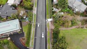 Metragem aérea do zangão da condução de carro abaixo da estrada suburbana vídeos de arquivo