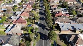 Metragem aérea do zangão da condução de carro abaixo da estrada suburbana para ao redor video estoque