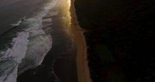 Metragem aérea do zangão das ondas de oceano que quebram antes da costa no por do sol Bali, Indonésia video estoque