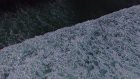 Metragem aérea do zangão das ondas de oceano que quebram antes da costa no por do sol Bali, Indonésia filme