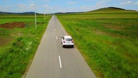 Metragem aérea do zangão de um carro que viaja ao longo de uma estrada secundária filme