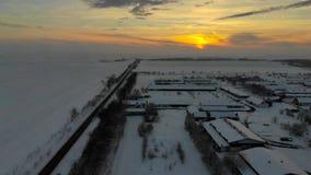 Metragem aérea do zangão 4K da vila na planície coberta com a neve Tempo nebuloso branco do inverno filme