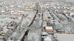 Metragem aérea do zangão 4K da vila na planície coberta com a neve Tempo nebuloso branco do inverno video estoque
