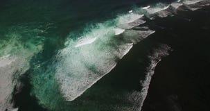 Metragem aérea do zangão 4k das ondas de oceano que quebram antes da costa Bali, Indonésia filme