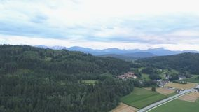 Metragem aérea dos carros que movem sobre uma estrada perto de uma vila entre campos e florestas verdes no por do sol Montanhas n filme