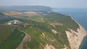 Metragem aérea, parte da terra no mar, vista bonita do monte gramíneo, movimento lento vídeos de arquivo