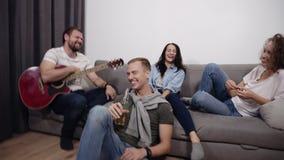 Metragem acelerada dos amigos que têm o divertimento junto na sala de visitas Homem farpado que senta-se no sofá com acústico vídeos de arquivo