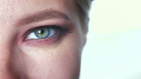Metragem bonita do close up do olho verde da mulher caucasiano que olha da câmera inferior do tat e que não pisca, composição vídeos de arquivo