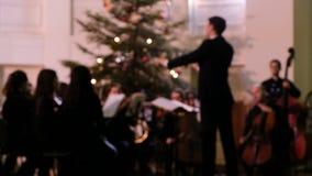 Metragem borrada - o condutor de orquestra da câmara controla os músicos durante um concerto vídeos de arquivo