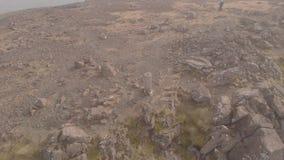 Metragem circular aérea do ponto do trig da cimeira de uma montanha rochosa enorme majestosa de Munro em Escócia Bla Bheinn filme