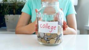 Metragem conceptual do close up 4k do dinheiro da economia da jovem mulher para a educação na faculdade vídeos de arquivo