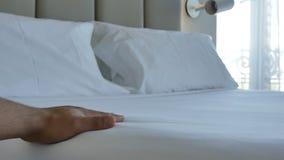 Metragem confortável branca de acariciamento do colchão 4k da cama da mão do close up vídeos de arquivo