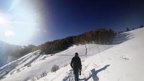 Metragem da aventura do homem do snowboarder, andando às montanhas nevado dos cumes filme
