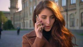 Metragem da cara bonita da mulher do caucaisna que tem a conversa telefônica, falando o straignt stadning da astúcia perto da câm filme