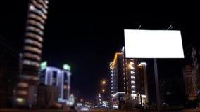 Metragem da cena urbana do lapso de tempo com um quadro de avisos vazio iluminado no lado de uma rua com os carros no movimento vídeos de arquivo