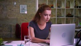 A metragem da fêmea caucasiano bonita está tentando duramente ao lobo, usando seu computador, datilografando focalizou ao sentar  filme