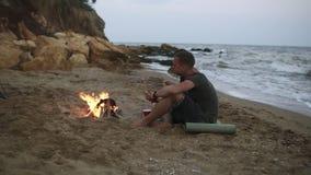 Metragem da vista geral de um par novo despreocupado que senta-se perto da fogueira na praia vazia na noite A menina está na filme