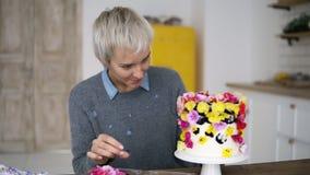 A metragem da vista geral da mulher com cabelo cinzento curto decora o bolo branco pequeno com as flores coloridas na cozinha mod filme
