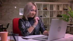 Metragem de dançar e de relaxar a fêmea caucasiano loura que se está sentando apenas no desktop no escritório do tijolo perto do  video estoque