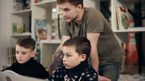 Metragem de dois meninos e de seu professor masculino novo do programador em uma sala de aula que aprendem como usar o portátil a video estoque