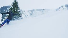 A metragem de homens do snowboarder e do esquiador jejua equitação em montanhas vídeos de arquivo