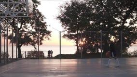 A metragem de Stedicam do lado de uma moça faz um tiro à rede do basquetebol Fora, as árvores e o sol brilham no vídeos de arquivo