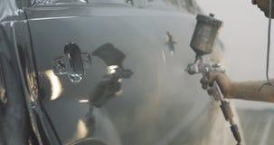 Metragem de um carro que está sendo pintado e envernizado em uma câmara da pintura que enverniza um carro preto video estoque