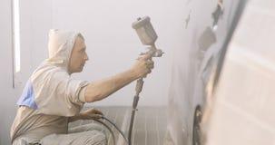 Metragem de um carro que está sendo pintado e envernizado em uma câmara da pintura que enverniza um carro preto vídeos de arquivo