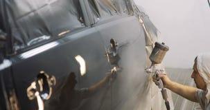 Metragem de um carro que está sendo pintado e envernizado em uma câmara da pintura que enverniza um carro preto filme