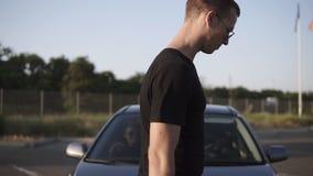 Metragem de um jovem - o homem e a mulher obtêm no carro Equipe é porta de carro aberta para sua amiga e vão então ao vídeos de arquivo