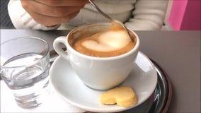 Metragem de uma mulher que agita uma xícara de café em uma cafetaria video estoque