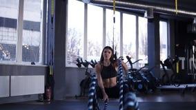 Metragem dianteira de cordas de luta da mulher de meia idade determinada no gym durante o exercício do cruz-treinamento Movimento filme
