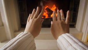 Metragem do close up da jovem mulher que aquece suas mãos em fogo ardente no dia de inverno frio filme