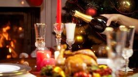 Metragem do close up 4k do champanhe de derramamento no vidro no jantar de Natal video estoque