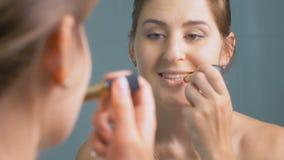 Metragem do close up 4K da jovem mulher bonita que aplica o batom vermelho no espelho no banheiro filme