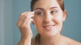 Metragem do close up 4K da jovem mulher que arranca suas sobrancelhas com a pinça no banheiro video estoque