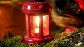 Metragem do close up 4k da lanterna vermelha com vela ardente no ramo de árvore do Natal Fundo perfeito para o inverno video estoque