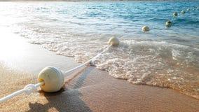 Metragem do close up 4k da linha de flutuação de boias no mar no por do sol video estoque