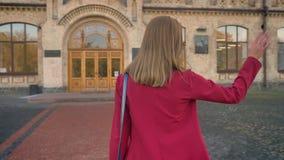 Metragem do estudante novo fêmea novo que anda à entrada da universidade que acena com sua mão, cumprimento, da parte traseira filme