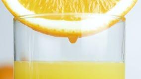 Metragem do movimento lento do close up da gota que cai lentamente no vidro do suco de laranja filme