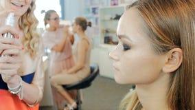 Metragem do movimento lento do close up do maquilhador profissional que aplica a composi??o na cara dos modelos antes do desfile  filme
