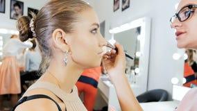 Metragem do movimento lento do close up do maquilhador profissional que aplica a composi??o na cara dos modelos antes do desfile  vídeos de arquivo