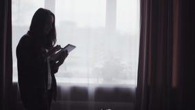 Metragem do movimento lento com uma silhueta de cabelos compridos nova da mulher que esteja usando o dispositivo móvel dentro filme