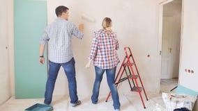Metragem do movimento lento da dança alegre feliz dos pares ao pintar paredes com o rolo de pintura em seu apartamento novo abaix video estoque