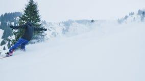 Metragem do movimento lento da equitação do snowboarder e do esquiador em montanhas vídeos de arquivo