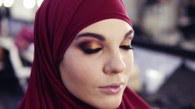 Metragem do movimento lento da menina de vista caucasiano lindo com hijab chiffon roxo em sua cabeça que obtém toques finais de video estoque