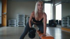 Metragem do movimento lento do exercício atrativo da jovem mulher com os pesos que inclinam seu joelho em um banco no gym vazio c video estoque